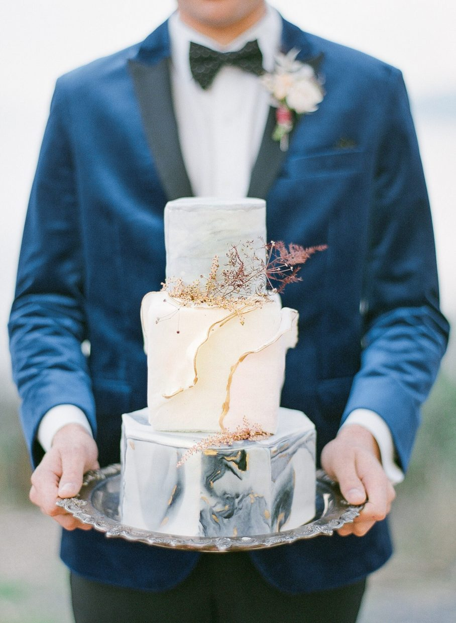groom holding a wedding cake