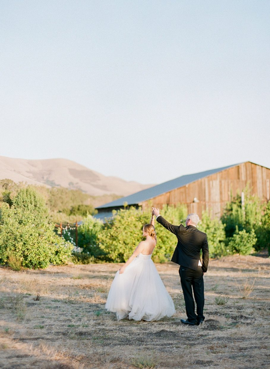 Couple dancing in front of wooden house