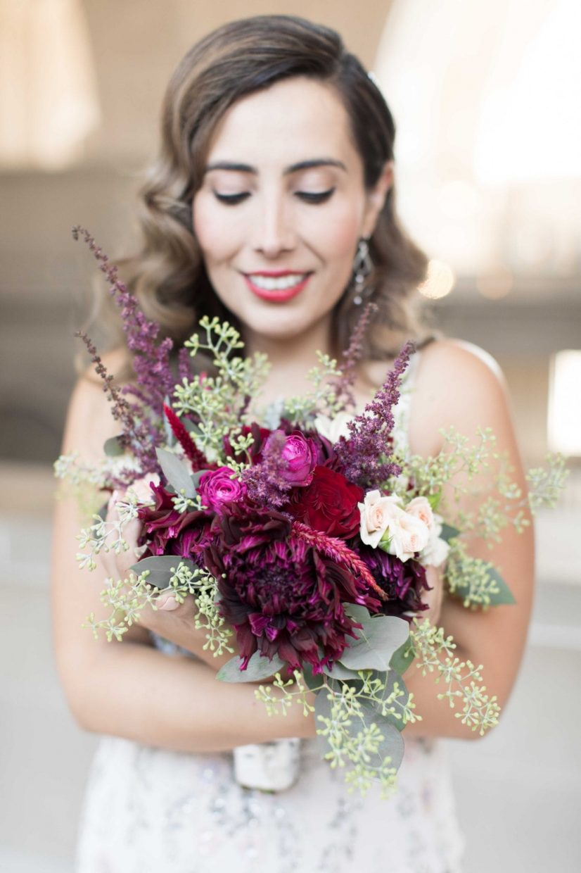 bride hugging her maroon flowers