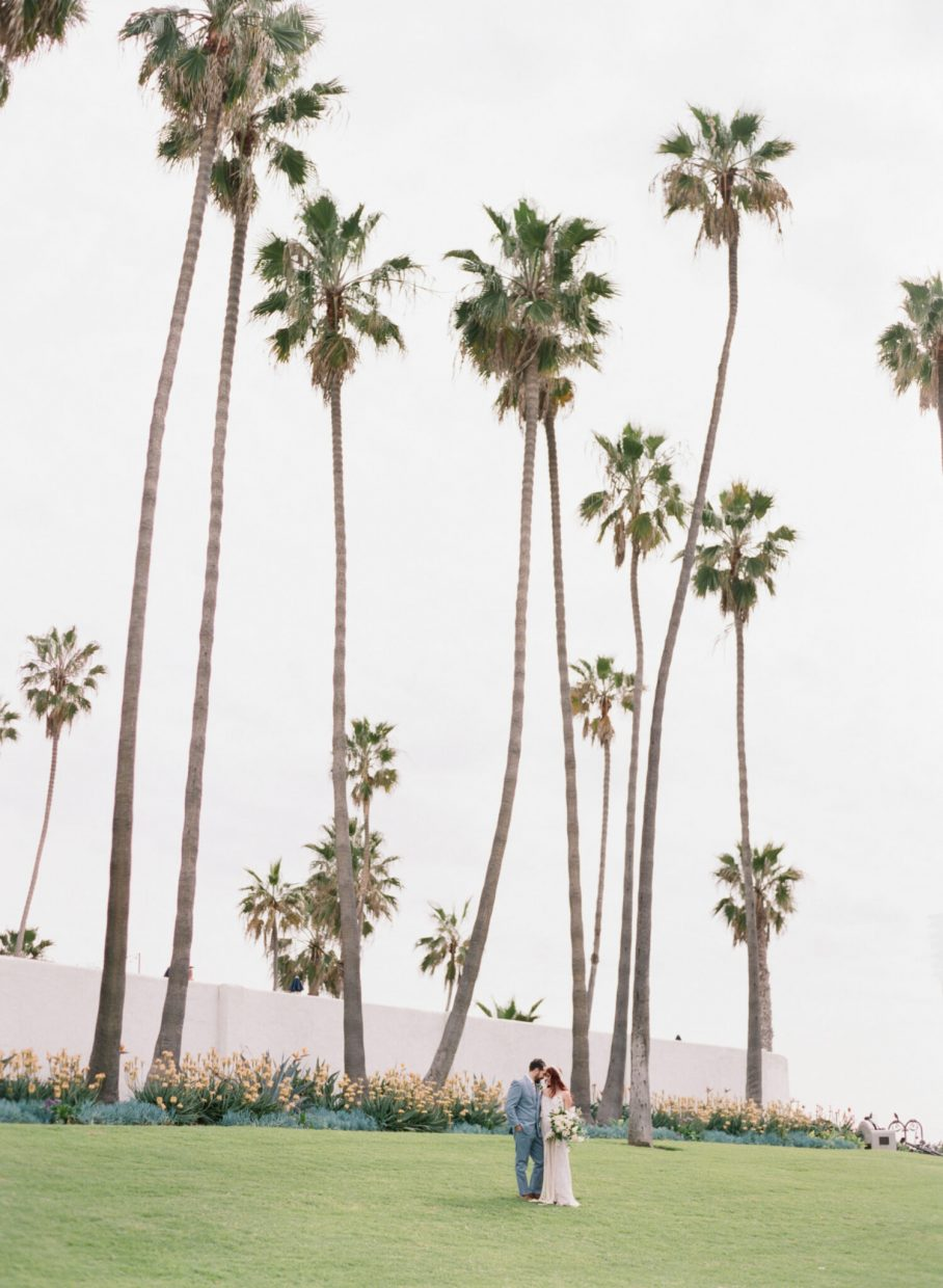 woman and man posing under palm trees in SoCAL