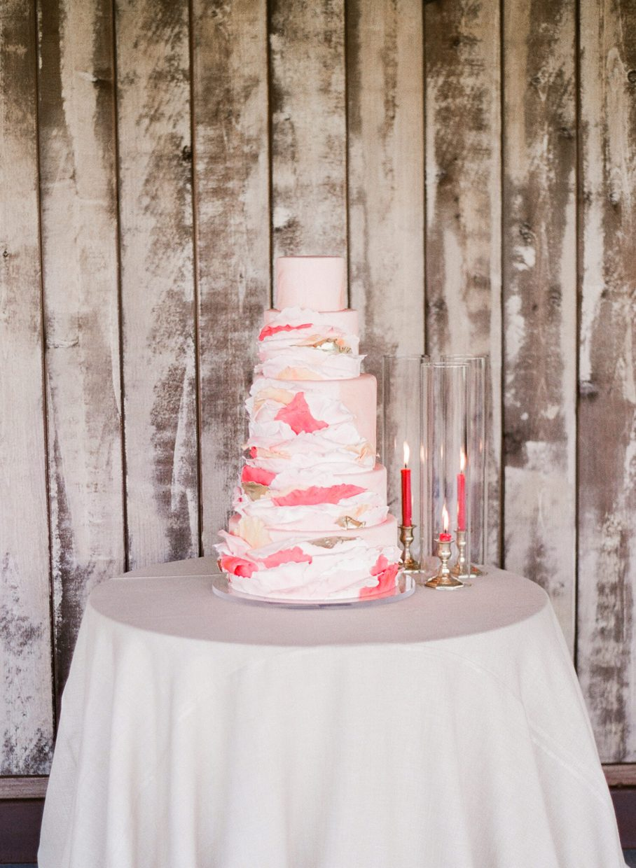 Rosé inspired wedding cake against wood barn