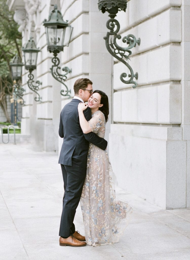 Lena Hall hugging her groom with a smile in front of war memorial building