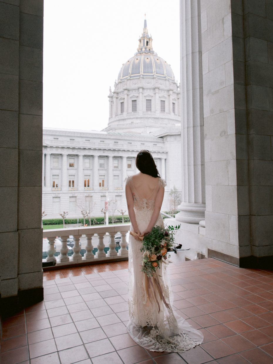 flowers behind her back staring at the City Hall