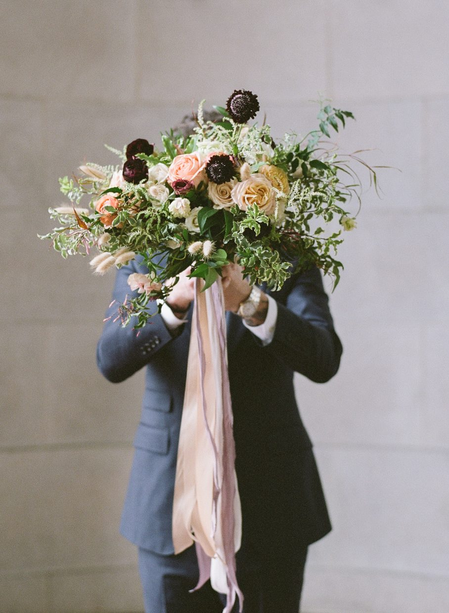 flowers in front of grooms face