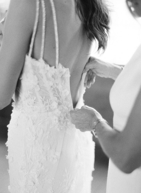 mom zipping up brides dress