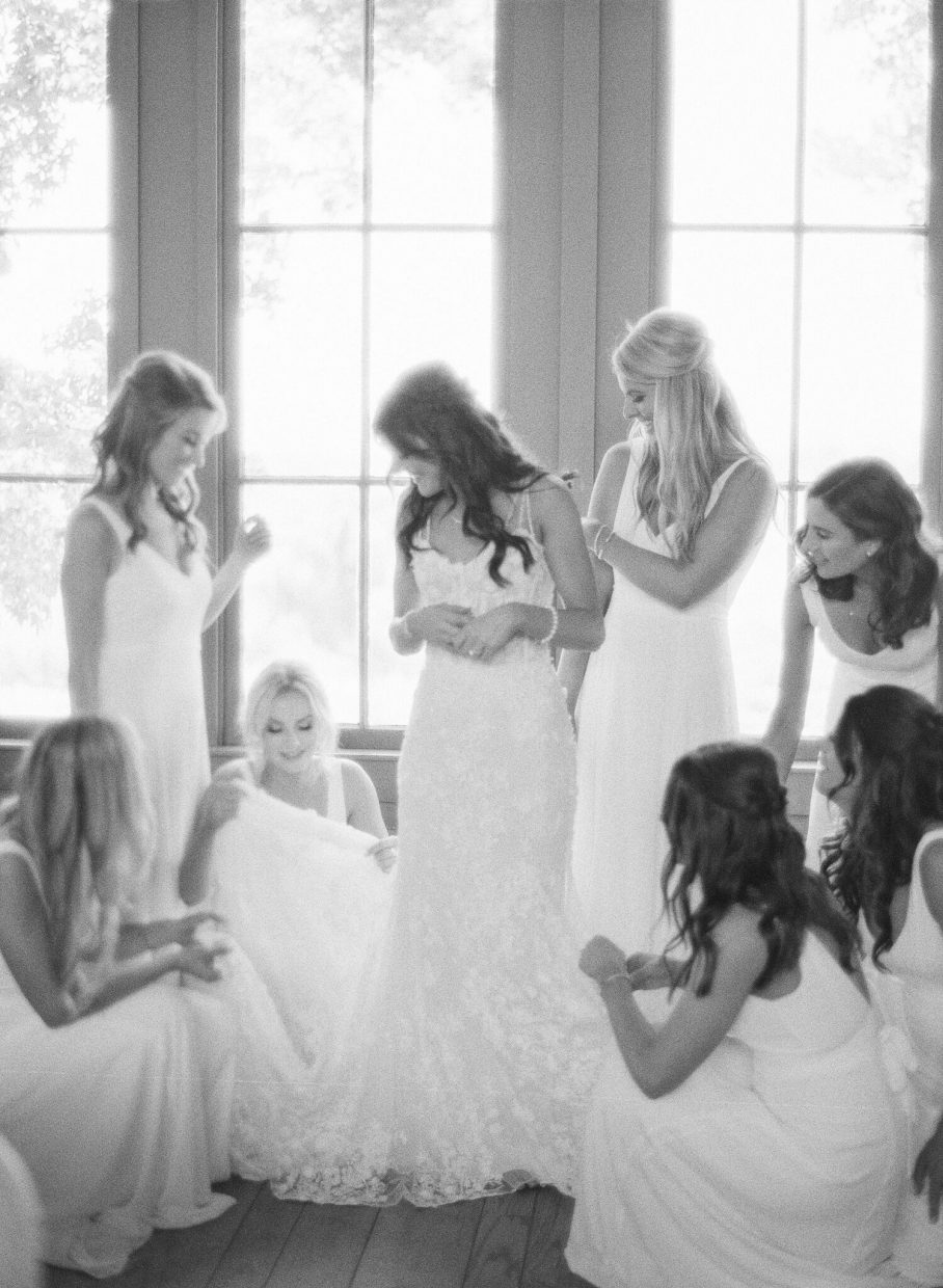 Bridesmaids surrounding the bride as she dresses