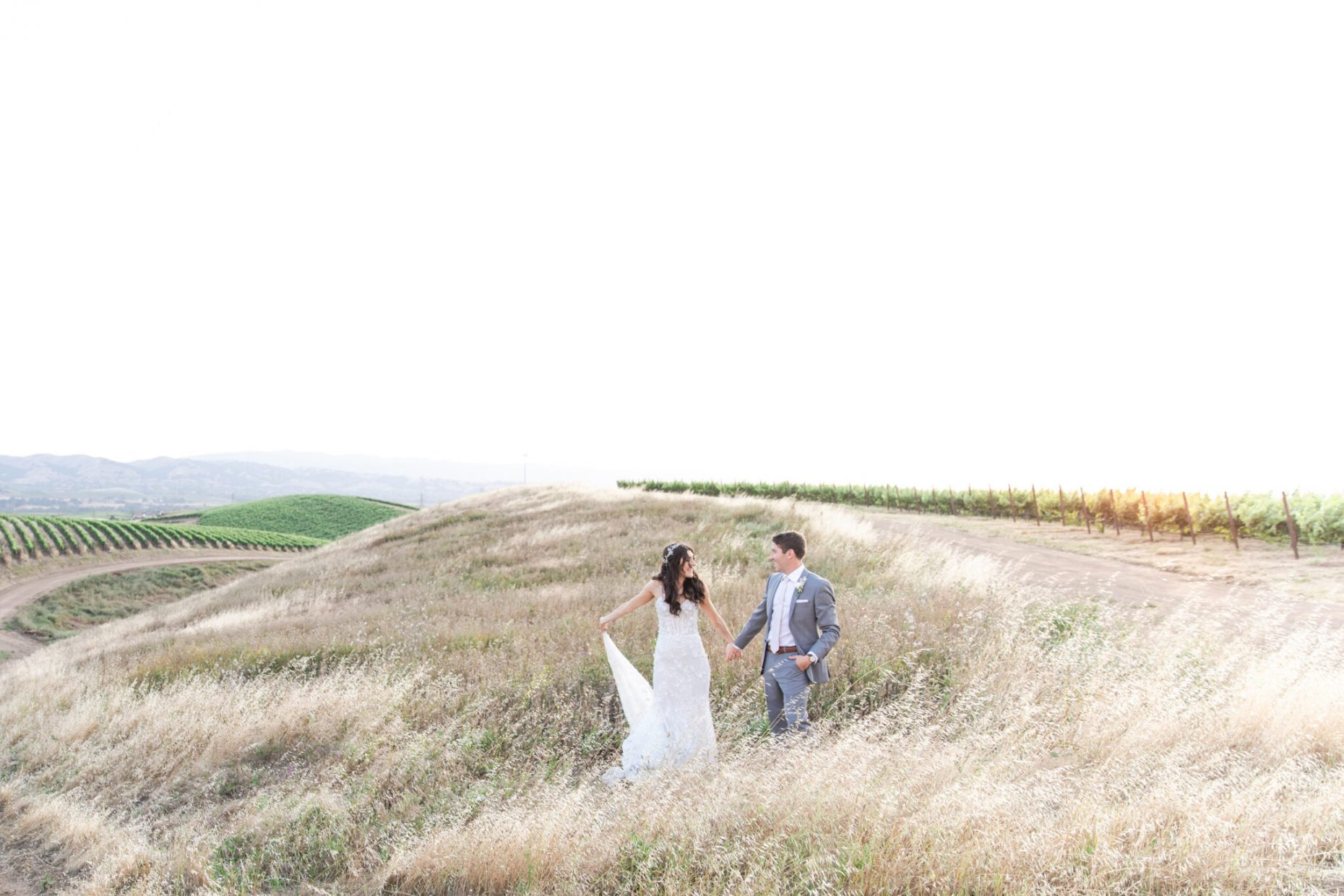 Bride and Groom dancing in a field of vineyards