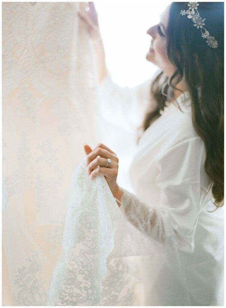Bride holding her dress looking up