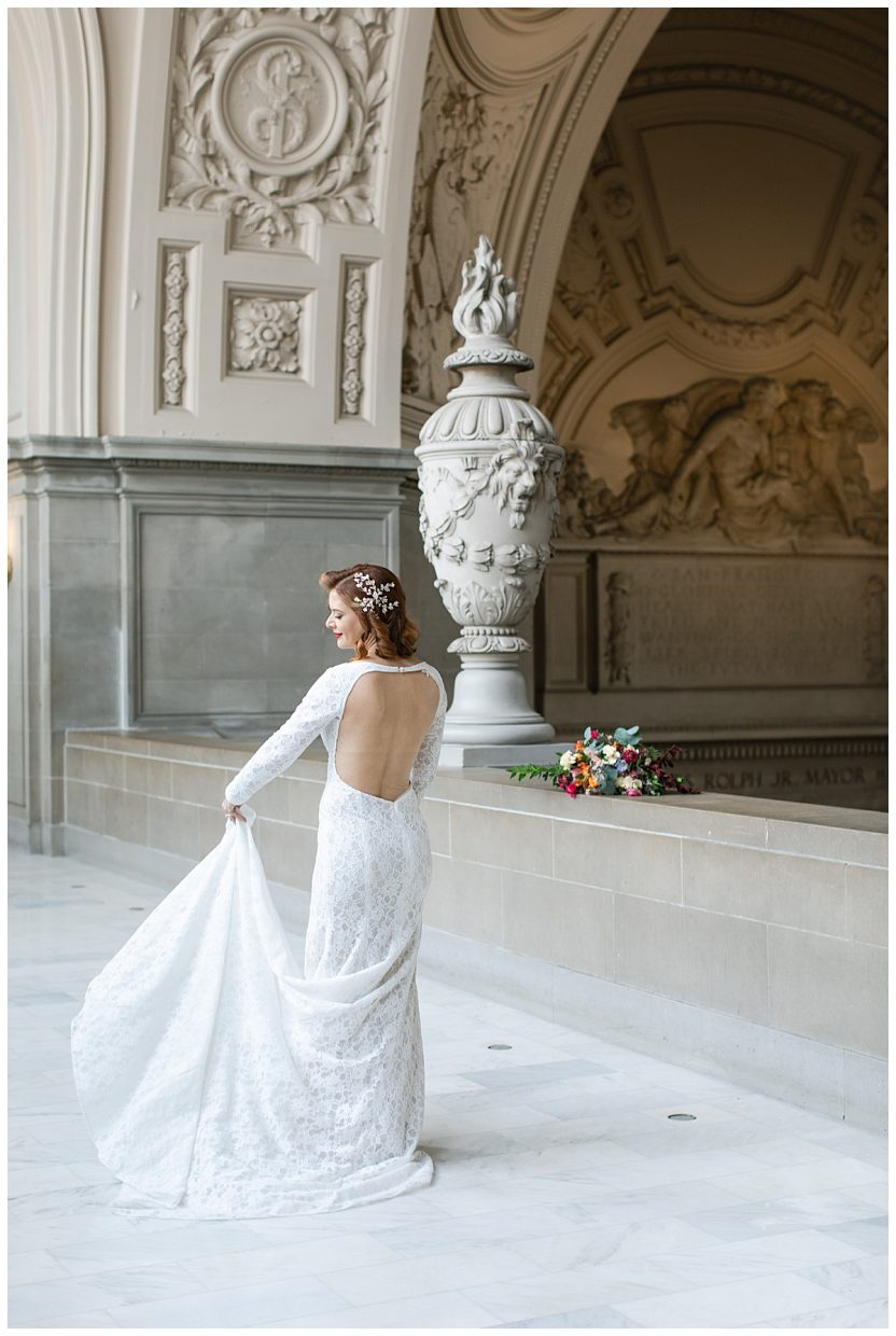 bride holding the train of her dress in venue