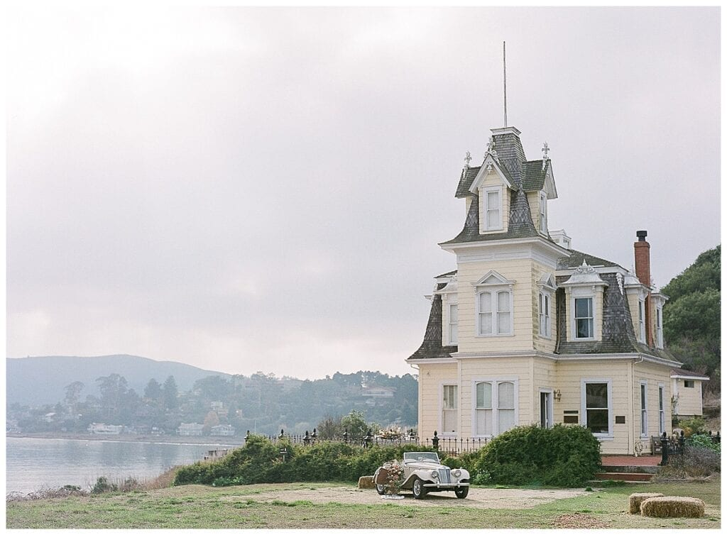 Lyford House on the cliff with an old car