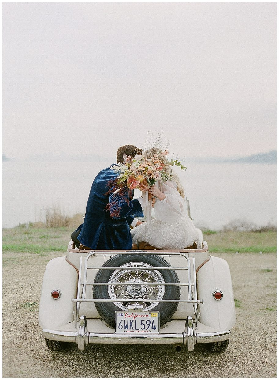 couple kissing behind flowers on old MG vintage car