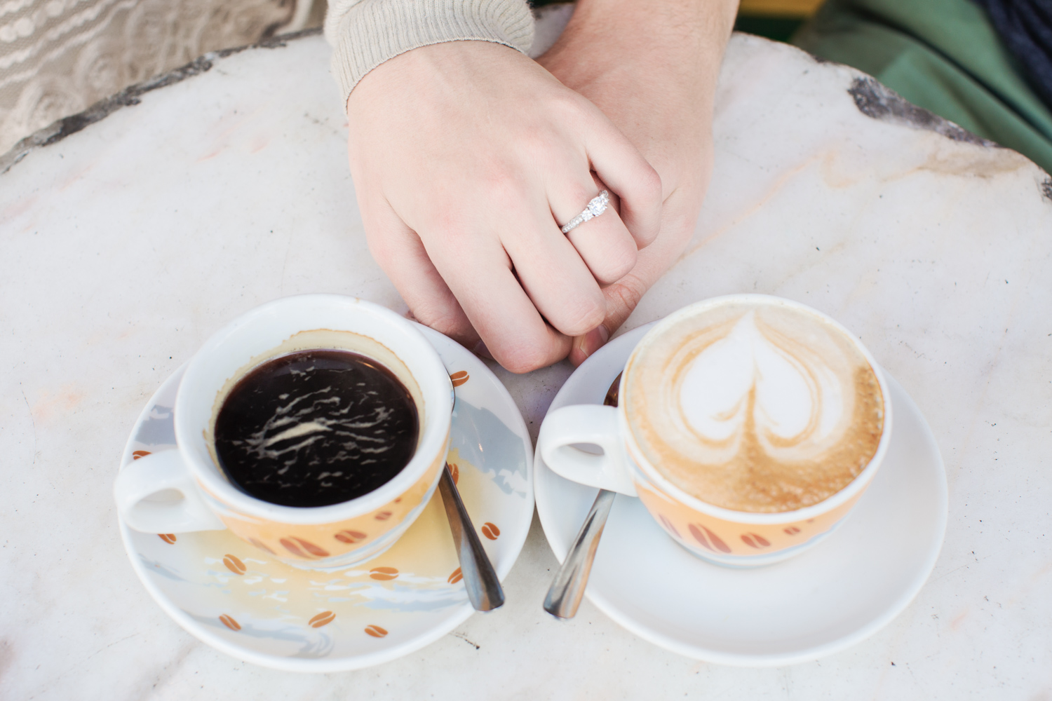 Holding hands with coffee and diamond ring