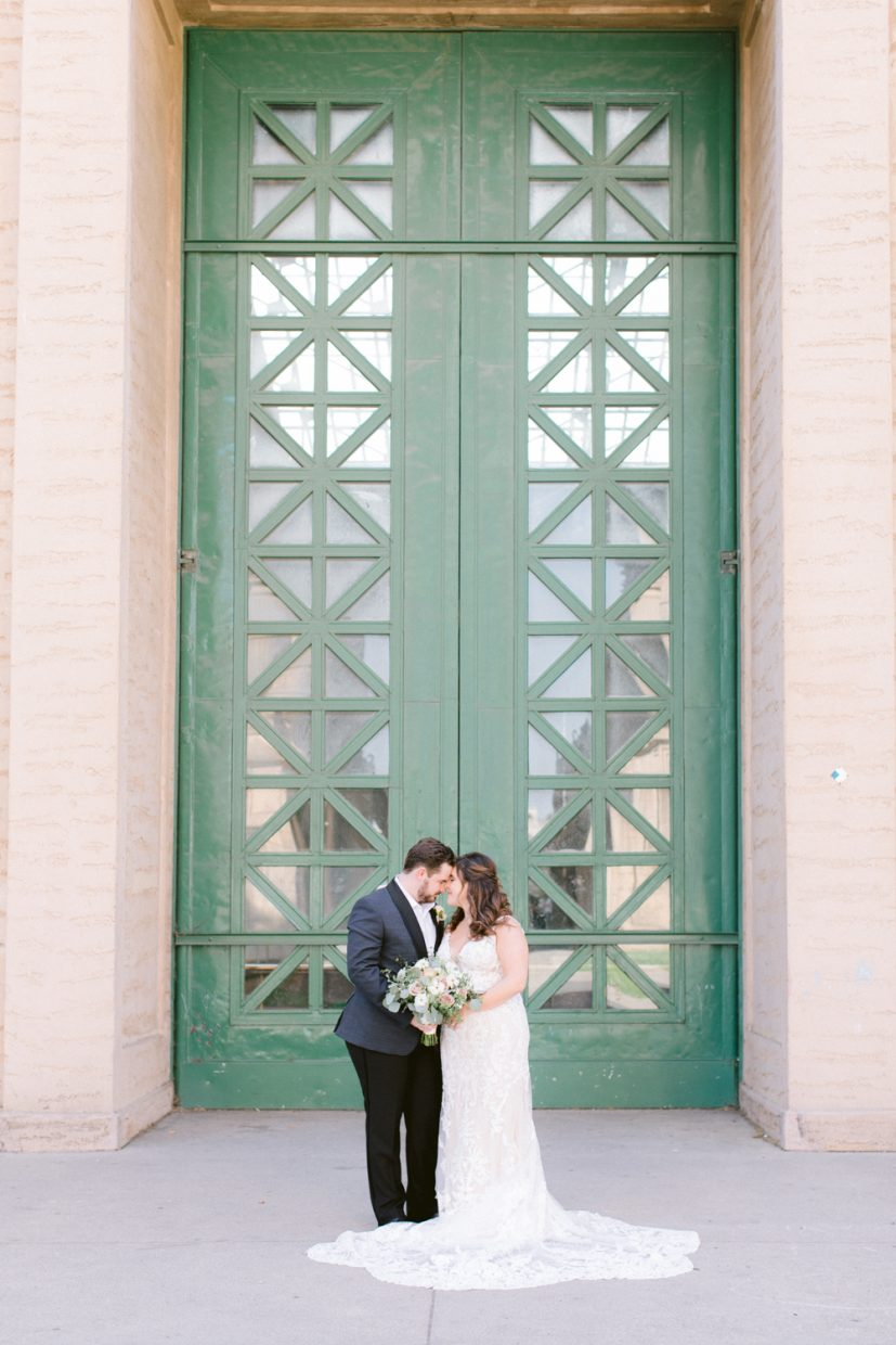 Couple standing in front of green door at Palace of Fine Arts