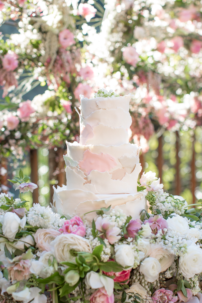 Wedding cake wrapped in flowers and light