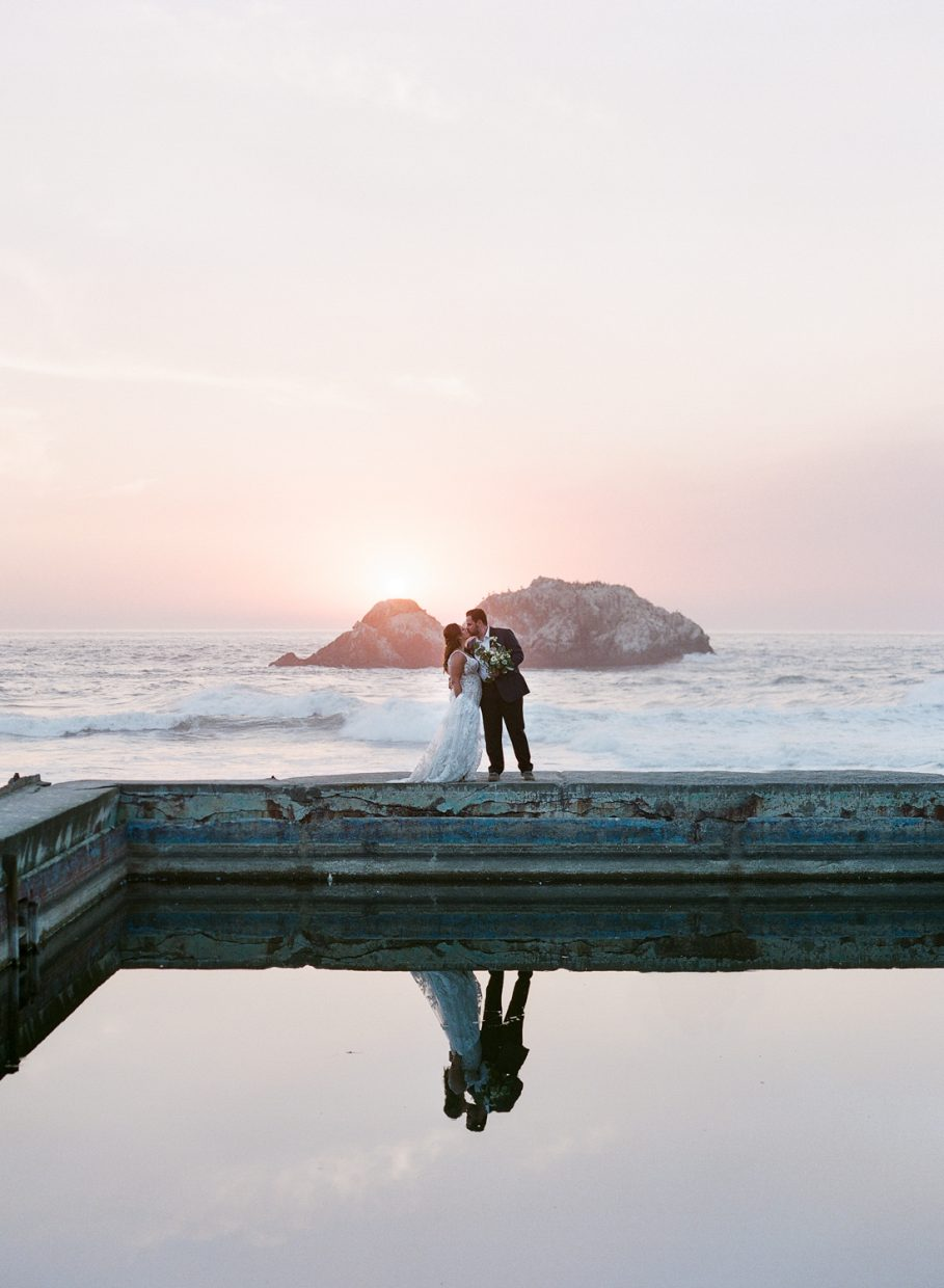 Bride & Groom standing in Sutro Baths with golden sunset