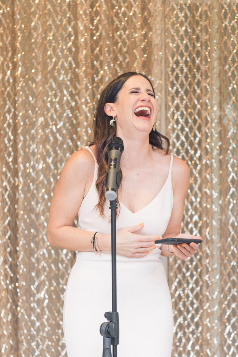 Bridesmaid laughing while giving a speech
