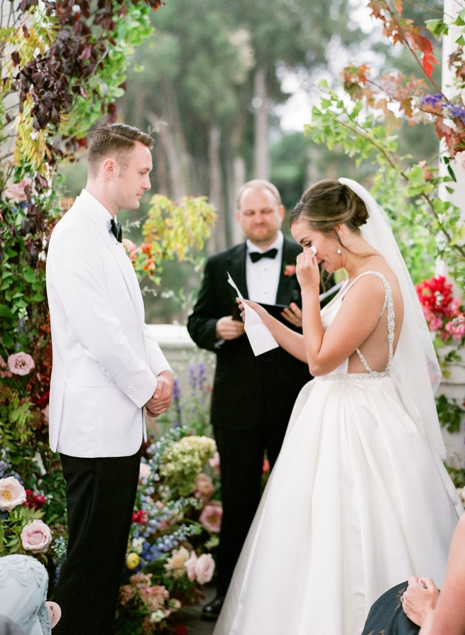 bride wiping her tears away during vows